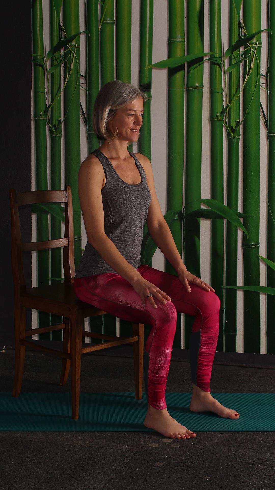 Grundposition Dehnung Gesäßmuskulatur, auf Stuhlkante aufrecht sitzend, Beine im rechten Winkel, Füße am Boden. Übung gegen Rückenschmerzen