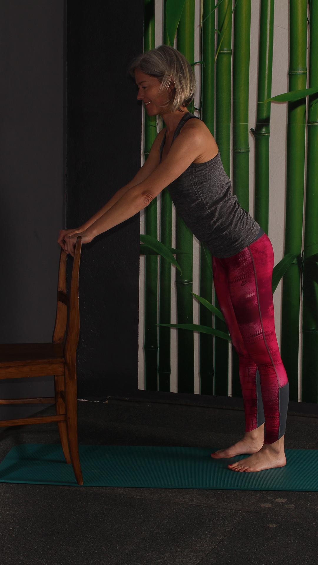 Grundposition Dehnung langer Rücken. Frau hat Hände am Stuhl, steht 2 Schritte hinterm Stuhl, Oberkörper aufrecht. Übung gegen Rückenschmerzen