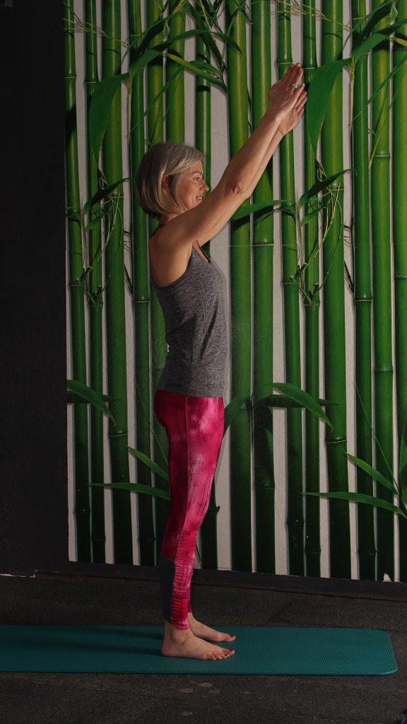 Grundposition für Kniebeuge. Aufrechter Stand, Knie minimal gebeugt, Arme in Vorhalteposition, Übung gegen Rückenschmerzen