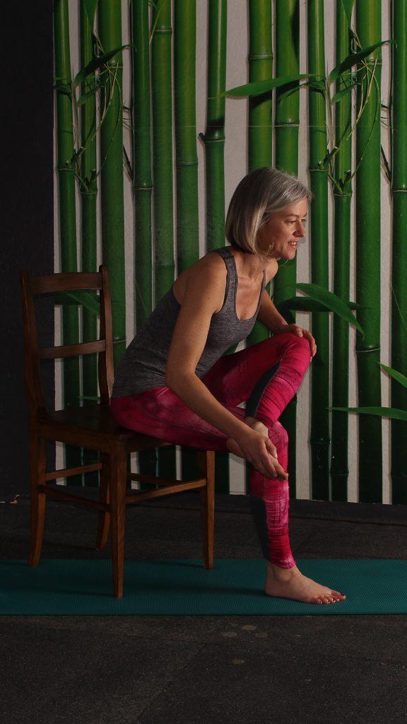 Endposition für Dehnung Gesäßmuskulatur, Rechter Fuß auf linkem Oberschenkel, Oberkörper gerade nach vorne geneigt. Übung gegen Rückenschmerzen