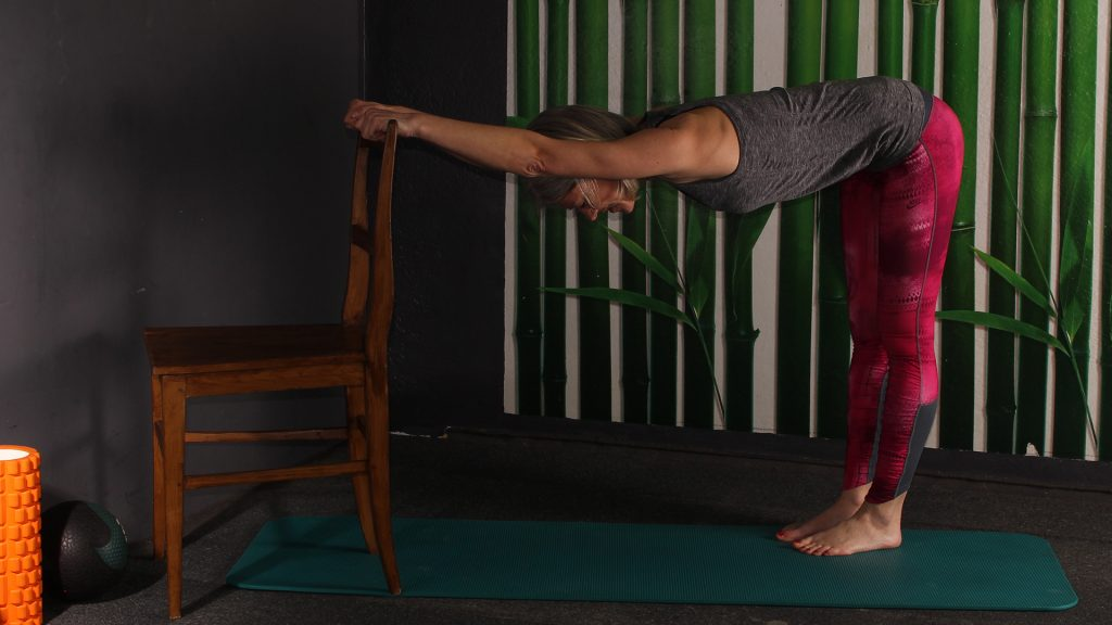 Endposition Dehnung langer Rücken. Frau hat Hände am Stuhl, steht 2 Schritte hinterm Stuhl, Oberkörper nach vorne tiefgeneigt.