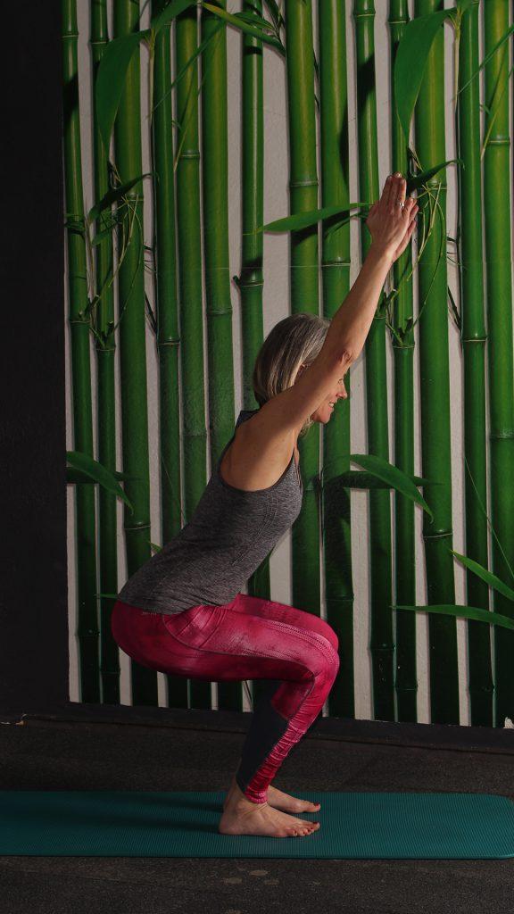 Endposition Kniebeuge, Knie gebeugt ca. 90 Grad, Rücken gerade, leicht vorgeneigt, Arme in Verlängerung des Oberkörpers, Übung gegen Rückenschmerzen